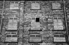 De zwart-wit verlaten verlaten oude baksteen industriële bouw met rood schilderde gebroken ingescheept op rottende vensters stock fotografie