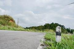 De zwart-witte kilometers van de stenen concrete pijler op de weg zijn behandeld met gras Met een grijze hemel, rotsachtige kilom stock afbeelding