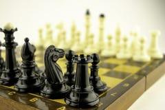 De zwart-witte schaakstukken bevinden zich op een schaakbord v??r het begin van het spel stock foto's