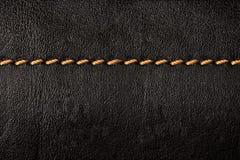 De zwarte achtergrond van de leertextuur met oranje naden Stock Foto's