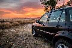 De zwarte al terreinauto hield in aard met de zonsondergang in s op Stock Foto's