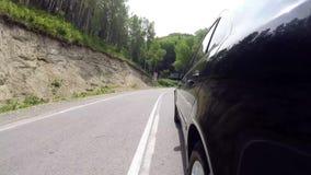 De zwarte auto beweegt zich langs een windende bergweg