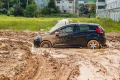 De zwarte auto plakte in de modder Stock Foto