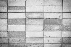 De zwarte bakstenen muur als achtergrond toont schade Stock Afbeeldingen