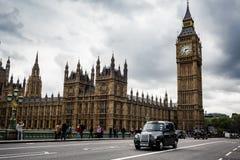 De zwarte cabine gaat voetgangers over die voor Big Ben en Huizen van het Parlement op de Brug van Westminster lopen N Stock Afbeeldingen