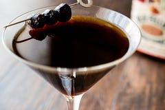 De zwarte Cocktail van Manhattan met olijven op donkere houten oppervlakte stock fotografie