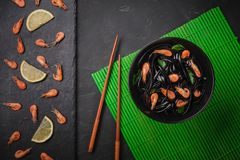 De zwarte deegwaren van Fettuccine van de pijlinktvisinkt met garnalen of garnalen, peterselie, Spaanse peper in wijn en botersau stock afbeelding