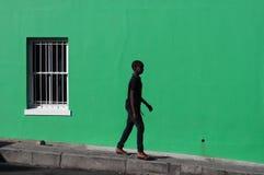 De zwarte die jongen door de groene muur wordt gelopen, kijkt als een schaduw, in het Kwartstraat van BO Kaap, Cape Town, Zuid-Af stock foto's