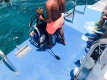 De zwarte duikbus, Arabier, Moslim treft voor het duiken voorbereidingen, duiken, die in het overzees, de oceaan, het blauwe wate royalty-vrije stock afbeelding
