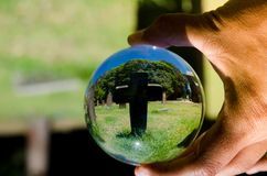 De zwarte dwarsfotografie van de steenbegraafplaats in de duidelijke bal van het kristalglas royalty-vrije stock fotografie