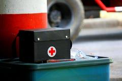 De zwarte eerste hulp die op de grote groene plastic doos zetten voor neemt zorg en controleert ziekte of ziekte stock afbeelding