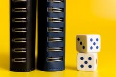 De zwarte en blauwe notitieboekjes op een gele achtergrond met wit dobbelen royalty-vrije stock foto's