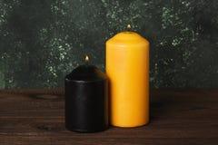 De zwarte en gele brandende kaars voor Halloween op een donkere rug Stock Afbeelding
