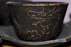 De zwarte en gouden kop van de gietijzerthee Stock Foto's