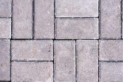 De zwarte en grijze keien van een voetpad zijn gelegd in een geometrisch patroon royalty-vrije stock afbeeldingen