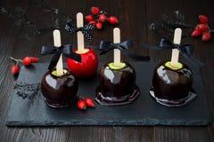 De zwarte en rode appelen van de vergiftkaramel Traditioneel dessertrecept voor Halloween-partij Stock Foto's