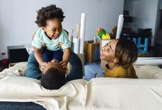 De zwarte familie geniet samen van kostbaar tijdgeluk stock afbeelding