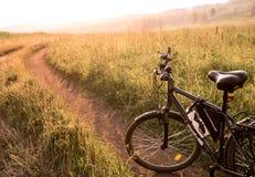 De zwarte fiets van het land bij zonsopgang of zonsondergang Stock Afbeeldingen
