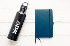 De zwarte fles en het notitieboekje van het aluminium opnieuw te gebruiken water royalty-vrije stock foto's