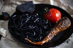 De zwarte gekleurde noedels van de pijlinktvisinkt met klusje-geroosterde creatieve tomaat, stock afbeeldingen