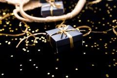 De zwarte giftdozen met gouden lint pop uit van gouden zak glanzen achtergrond Sluit omhoog Stock Foto