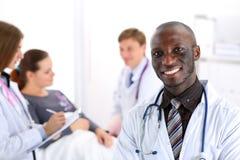 De zwarte glimlachende mannelijke arts kijkt in camera stock afbeeldingen