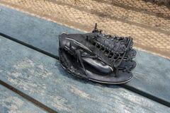 De zwarte handschoen van het leerhonkbal op de bankbeslagen schermt het gieten stock fotografie