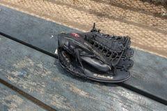 De zwarte handschoen van het leerhonkbal op de bankbeslagen schermt het gieten royalty-vrije stock afbeeldingen