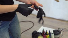 De zwarte handschoenen van de meisjeskleding voor het airbrushing stock videobeelden