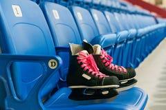 De zwarte hockeyvleten met pingelen schoenveters op de stoel op het lege stadion stock foto