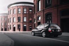 De zwarte Houtvester van autosubaru parkeerde dichtbij moderne rode gebouwen in Moskou bij dag Stock Afbeeldingen