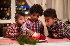 De zwarte kaarsen van jongens lichte Kerstmis Stock Afbeeldingen