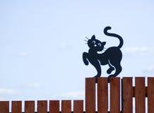 De zwarte kat op een omheining stock fotografie