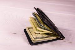 De zwarte klem van het leergeld met de honderd dollarsrekeningen op houten lijst royalty-vrije stock foto's