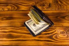De zwarte klem van het leergeld met de honderd dollarsrekeningen op houten lijst stock fotografie