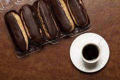 De zwarte koffie, chocolade Eclair, koffie in een witte Kop, witte schotel, op een bruine lijst, twee eclairs op papier bevindt z stock afbeeldingen