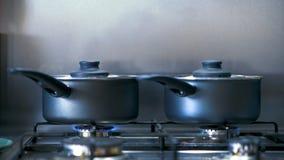 De zwarte kokende potten op een gas hob het uitzenden van stoom aangezien zij voedsel binnen koken stock video