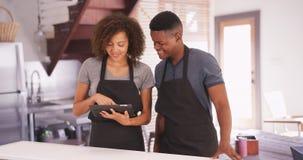 De zwarte man en de vrouw plannen hun recept op hun tablet Stock Foto's