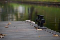 De zwarte meerpaal van de metaalmeertros op een houten pijler bij een meer, een exemplaarruimte, een detail met geselecteerde nad royalty-vrije stock afbeelding