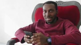 De zwarte mens gebruikt een smartphone om op Internet te communiceren stock videobeelden