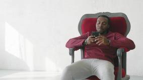 De zwarte mens gebruikt een smartphone om op Internet te communiceren stock footage
