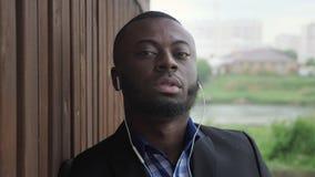 De zwarte mens in oortelefoons is het luisteren muziek bij stadsstraat tijdens regen stock videobeelden