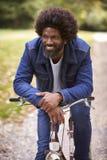 De zwarte midden oude mensenzitting op een fiets in een park, die op de sturen leunen die, vooraanzicht, sluit omhoog glimlachen stock foto