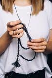 De zwarte parelt armband in meisjeshand Kan als maniertoebehoren worden gebruikt, ook aangezien het bidden parels, voor het telle stock foto