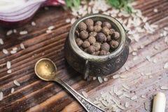 De zwarte peper in een wijnoogst sneed pepperbox, een kleine lepel, verspreide rijst op een donkere bruine houten achtergrond Stock Fotografie