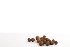 De zwarte peper werd geplaatst op een wit Stock Afbeeldingen
