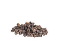 De zwarte peper werd geplaatst op een wit stock afbeelding