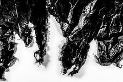 De zwarte plastiek gescheurde witte achtergrond van de huisvuildekking Royalty-vrije Stock Foto's