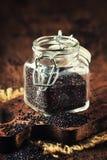 De zwarte quinoa zaden goten van glaskruik, de uitstekende achtergrond van de keukenlijst, selectief nadruk verticaal beeld royalty-vrije stock fotografie