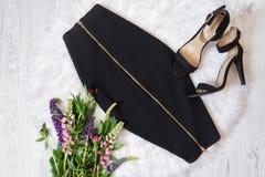 De zwarte rok van Midi met een ritssluiting en schoenen met wit bont, een boeket van bloemen modieus concept Royalty-vrije Stock Fotografie